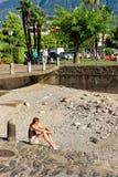 Женщина сидя на береге на курорте Ascona дорогом Стоковые Изображения