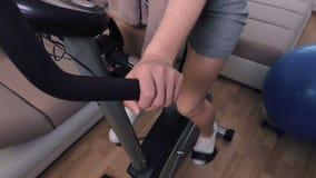 Женщина сидя на велотренажере сток-видео