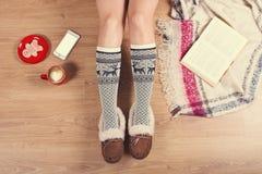 Женщина сидя на деревянном поле с чашкой кофе, телефоном, печеньем и книгой Конец-вверх женских ног в теплых носках с оленем VI Стоковые Фото