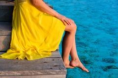 Женщина сидя на моле пляжа стоковые изображения rf