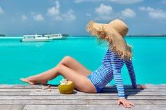 Женщина сидя на моле пляжа стоковые фотографии rf