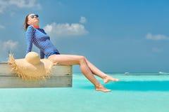 Женщина сидя на моле пляжа стоковое изображение rf