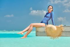 Женщина сидя на моле пляжа стоковое изображение