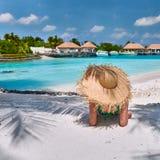 Женщина сидя на пляже под пальмой стоковые изображения rf