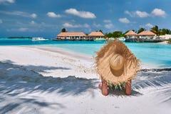 Женщина сидя на пляже под пальмой стоковое фото rf