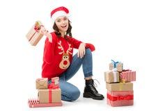 Женщина сидя на поле с подарками рождества стоковые изображения