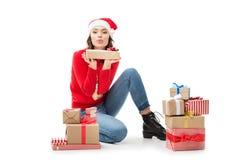 Женщина сидя на поле с подарками рождества стоковое изображение rf