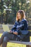 женщина сидя на скамейке в парке с портативным компьютером стоковые фотографии rf