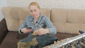 Женщина сидя на софе рассматривает и фотографирует, используя смартфон, собрание одежды джинсовой ткани вися на a видеоматериал