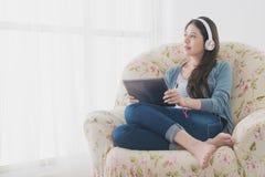 Женщина сидя на софе смотря внешний взгляд Стоковое Фото