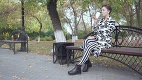 Женщина сидя на стенде в кофе парка, ослаблять и выпивать видеоматериал