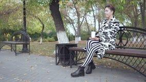 Женщина сидя на стенде в кофе парка, ослаблять и выпивать сток-видео