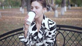 Женщина сидя на стенде в кофе парка, ослаблять и выпивать акции видеоматериалы