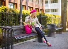 Женщина сидя на стенде в парке стоковые изображения