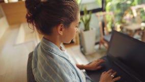 Женщина сидя на столе и печатая на ее ноутбуке видеоматериал