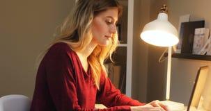 Женщина сидя на таблице используя компьтер-книжку 4k акции видеоматериалы