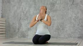 Женщина сидя на циновке йоги с размышлять жеста namaste Стоковое фото RF