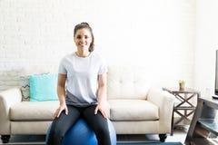 Женщина сидя на шарике фитнеса для разминки Стоковое Изображение