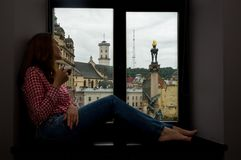 Женщина сидя на windowsill Стоковое Фото
