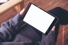 Женщина сидя перекрестный шагающий и держа черный ПК таблетки с пустым белым экраном на бедренной кости и деревянной предпосылке  Стоковые Фото