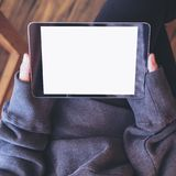 Женщина сидя перекрестный шагающий и держа черный ПК таблетки с пустым белым экраном на бедренной кости и деревянной предпосылке  Стоковая Фотография RF