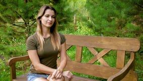 Женщина сидя самостоятельно на стенде Привлекательная девушка сидит на деревянной скамье среди зеленых цветов Женское усаживание  видеоматериал