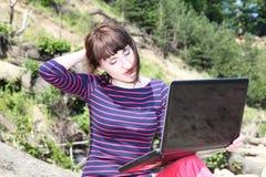 Женщина сидя с ее компьтер-книжкой Стоковое фото RF