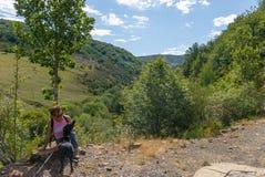 Женщина сидя с ее собакой на медном маршруте источника Природный парк Fuentes de Carrionas Испания стоковые фото