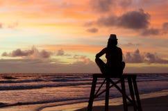 Женщина силуэта сидя на башне личной охраны наслаждаясь восходом солнца на пляже и ` s солнца излучает красящ небо Стоковое Фото