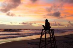 Женщина силуэта сидя на башне личной охраны наслаждаясь восходом солнца на пляже и ` s солнца излучает красящ небо Стоковые Фото