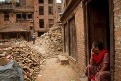 Женщина сидит вне ее теперь дома загубленного землетрясением в Bhaktapu стоковое изображение rf