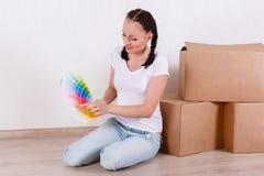 Женщина сидит в комнате около коробок Стоковая Фотография RF