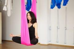 Женщина сидит в представлении лотоса в гамак практикуя воздушную йогу Стоковое фото RF