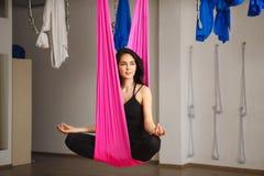 Женщина сидит в представлении лотоса в гамак практикуя воздушную йогу Стоковое Изображение