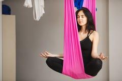 Женщина сидит в представлении лотоса в гамак практикуя воздушную йогу Стоковая Фотография