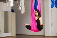 Женщина сидит в представлении лотоса в гамак практикуя воздушную йогу Стоковые Изображения RF