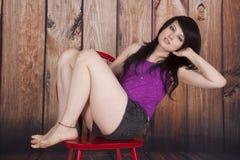 Женщина сидит красный стул деревянная предпосылка полагается назад стоковые изображения