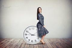 Женщина сидит на больших часах Стоковая Фотография RF