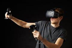 Женщина сидит на софе дома нося шлемофон виртуальной реальности стоковые изображения