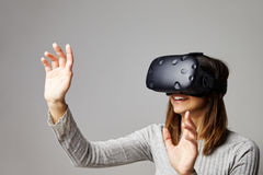 Женщина сидит на софе дома нося шлемофон виртуальной реальности стоковое фото rf