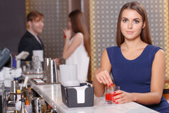 Женщина сидит на счетчике бара Стоковая Фотография
