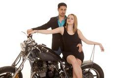 Женщина сидит человек мотоцикла за обоими взгляд стоковое изображение