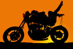 Женщина силуэта на мотоцикле кладет назад пальцы ноги вверх стоковые изображения rf
