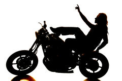Женщина силуэта на мотоцикле указывая вверх стоковое изображение