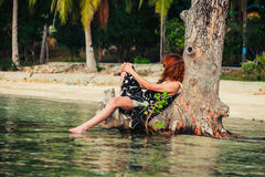 Женщина сидя вверх против дерева на тропическом пляже Стоковое Изображение RF