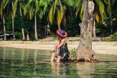 Женщина сидя вверх против дерева на тропическом пляже Стоковое Изображение