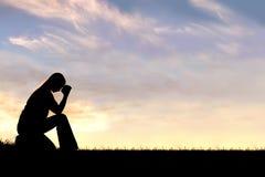 Женщина сидя вниз в силуэте молитве Стоковое Изображение RF