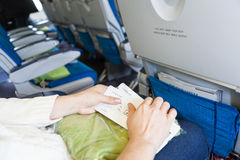 Женщина сидя в воздушных судн с посадочными талонами Стоковое Изображение RF