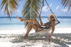 Женщина сидя в гамаке Стоковое Изображение