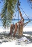 Женщина сидя в гамаке Стоковое фото RF